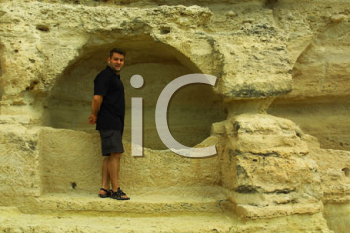 Royalty Free Photo of a Man Standing at a Rock Formation