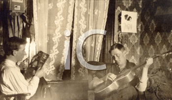 Royalty Free Photo of a Man Playing Guitar with a Man Reading