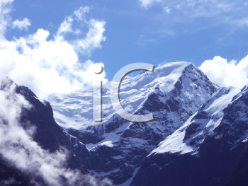 Royalty Free Photo of the Top of a Mountain Range and Clouds in the Sky