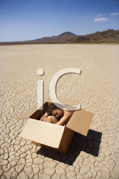 Royalty Free Photo of a Pretty Nude Young Woman Sitting in a Box in a Cracked Desert Landscape in California