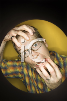 Royalty Free Photo of a Vignette of a Man on a Yellow Background Pulling at Face and Looking Stressed