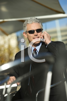 Royalty Free Photo of a Businessman Sitting at a Patio Table Outside Talking on a Cellphone and Smiling