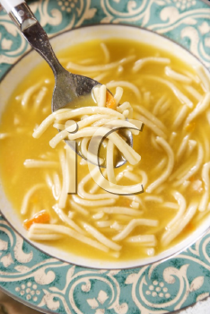 Royalty Free Photo of a Bowl of Chicken Noodle Soup With a Spoon