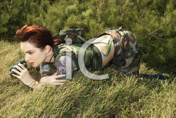 Royalty Free Photo of an Attractive Tattooed Woman in Camouflage Lying in Grass Looking Through Binoculars in Maui, Hawaii, USA