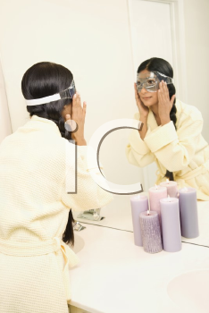Royalty Free Photo of a Woman Looking in the Mirror Adjusting an Eye Mask