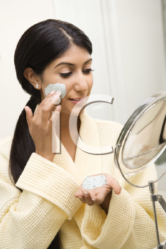 Royalty Free Photo of a Woman Applying Face Scrub in a Mirror