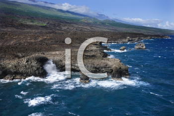 Aerial of Pacific ocean and Maui, Hawaii coast with waves hitting lava rocks.