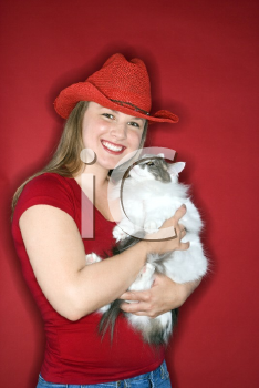 Royalty Free Photo of a Woman Wearing a Cowboy Hat Holding a Cat