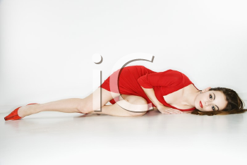 Attractive Caucasian  woman wearing red dress lying on floor looking at viewer.