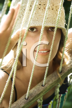 Royalty Free Photo of a Woman Looking Through a Hammock