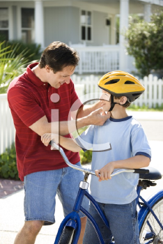 Royalty Free Photo of a Dad Strapping a Bicycle Helmet on His Son