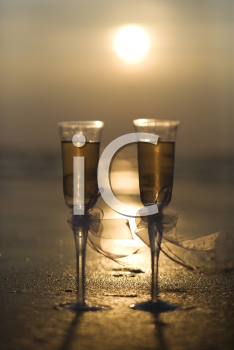 Royalty Free Photo of a Pair of Flute Glasses Filled With Champagne on a Beach at Sunset
