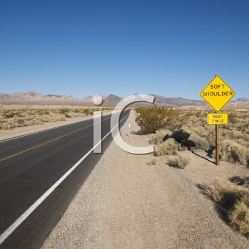Royalty Free Photo of a Road in a Desert With a Sign for Soft Shoulder and Mountains in the Distance