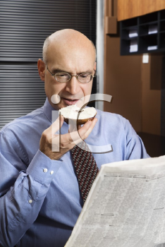 Royalty Free Photo of a Businessman Sitting in an Office Reading a Newspaper While Eating a Bagel