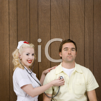 Royalty Free Photo of a Nurse  Checking a Male's Heartbeat