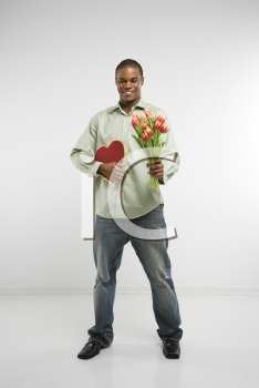 Royalty Free Photo of a Man Holding a Valentine Heart and Bouquet of Tulips Smiling