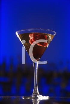 Royalty Free Photo of a Martini Cocktail With Raspberry Fruit Against a Glowing Blue Background