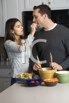 Royalty Free Photo of a Woman Feeding a Man at the Kitchen Counter While He Makes Salad