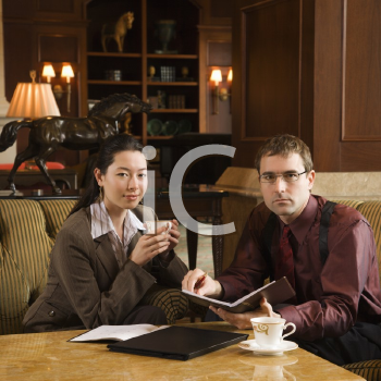 Royalty Free Photo of a Businessman and Businesswoman Drinking Coffee and Looking at a Portfolio