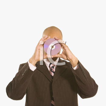 Royalty Free Photo of a Man Holding a Compact Disc Over His Face