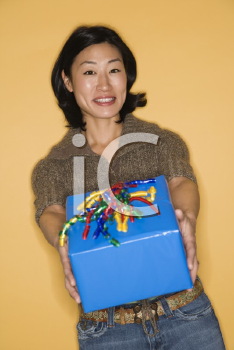 Pretty mid adult Asian woman holding out present.