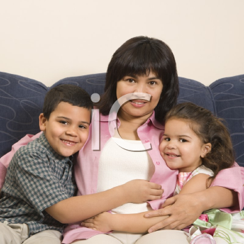 Royalty Free Photo of a Family Sitting on a Couch Hugging and Smiling