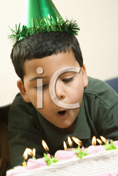 Royalty Free Photo of a Boy Wearing a Party Hat Blowing Out Candles on a birthday Cake