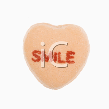 Royalty Free Photo of an Orange Candy Heart That Reads Smile