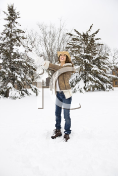 Royalty Free Photo of a Female Standing and Playing in the Snow Wearing a Straw Cowboy Hat