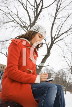 Low angle view of Caucasian young adult female in winter clothing sitting on park bench using PDA .