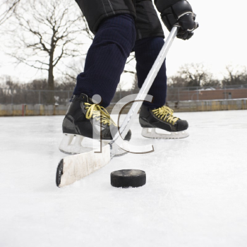 Royalty Free Photo of a Boy in an Ice Hockey Uniform Skating on an Ice Rink Moving a Puck