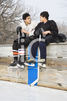 Royalty Free Photo of Two Boys in Ice Hockey Uniforms Sitting on the Sideline Talking