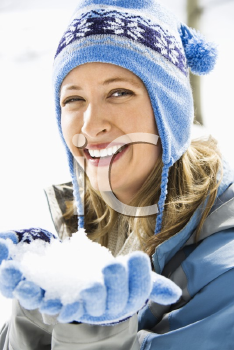 Royalty Free Photo of a Woman Wearing a Ski Hat and Gloves Holding a Snowball