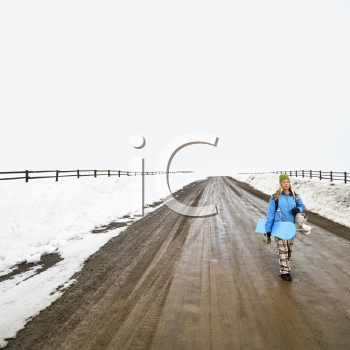 Young woman in winter clothes walking alone down muddy dirt road holding snowboard and boots.