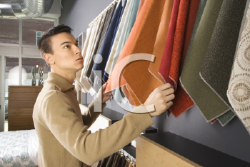 Royalty Free Photo of an Asian Male Looking at Fabric Swatches in a Retail Store