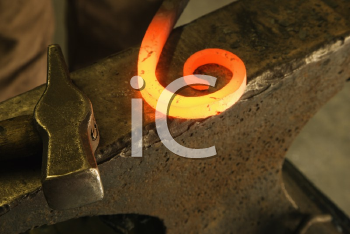 Royalty Free Photo of Hot Shaped Metal Laying on Anvil With Hammer