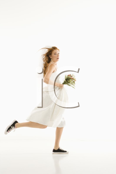 Royalty Free Photo of a Bride Running and Holding a Bouquet