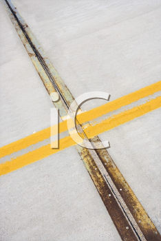 Royalty Free Photo of a Detail of Solid Double Yellow Lines in the Road in Cement