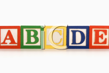Royalty Free Photo of Alphabet Toy Building Blocks Lined Up in a Row