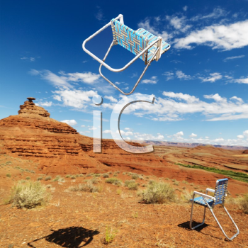 Royalty Free Photo of One Lawn Chair on the Ground and Other Up in the Air in a Desert Landscape