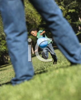 Royalty Free Photo of a Son Running and Kicking a Ball Towards His Father in a Park