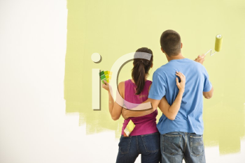 Royalty Free Photo of a Couple Standing in Front of a Partially Painted Wall With Arms Around Each Other
