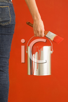 Royalty Free Photo of a Woman Holding a Paintbrush and Paint Can