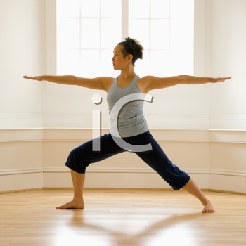 Royalty Free Photo of a Woman Doing Yoga Warrior Pose