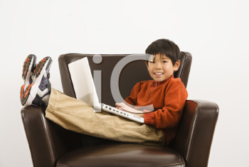 Royalty Free Photo of a Boy With a Laptop Computer Sitting in a Chair