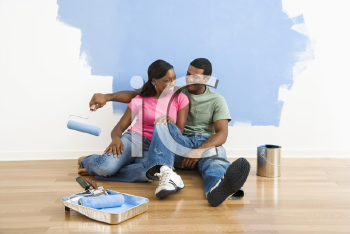 Royalty Free Photo of a Couple Sitting and Relaxing By a Half Painted Wall