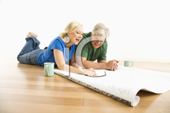 Royalty Free Photo of a Couple Lying on the Floor Looking and Discussing Architectural Blueprints