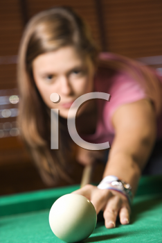 Young woman concentrating while shooting pool. Vertical shot.