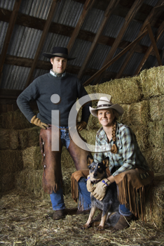 Attractive young man and woman with an Australian Shepherd in a barn. Bales of hay are in the background. Vertical shot.
