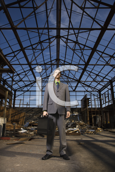 Young businessman stands in an abandoned building holding a briefcase with a serious look on his face. Vertical shot
